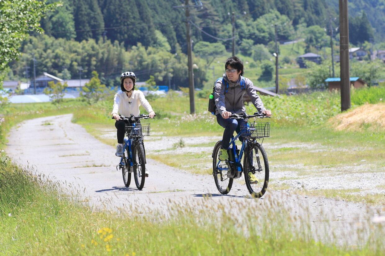 電動自転車で田舎をサイクリングする若者