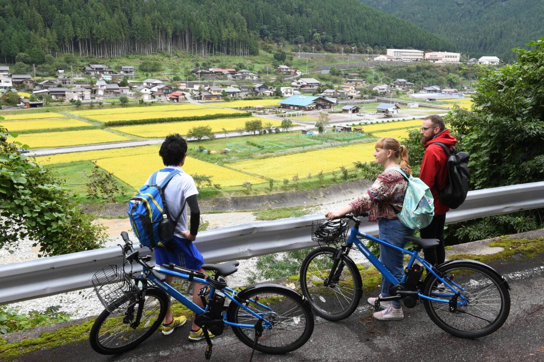 下呂の田園風景を眺めるサイクリングツアー客