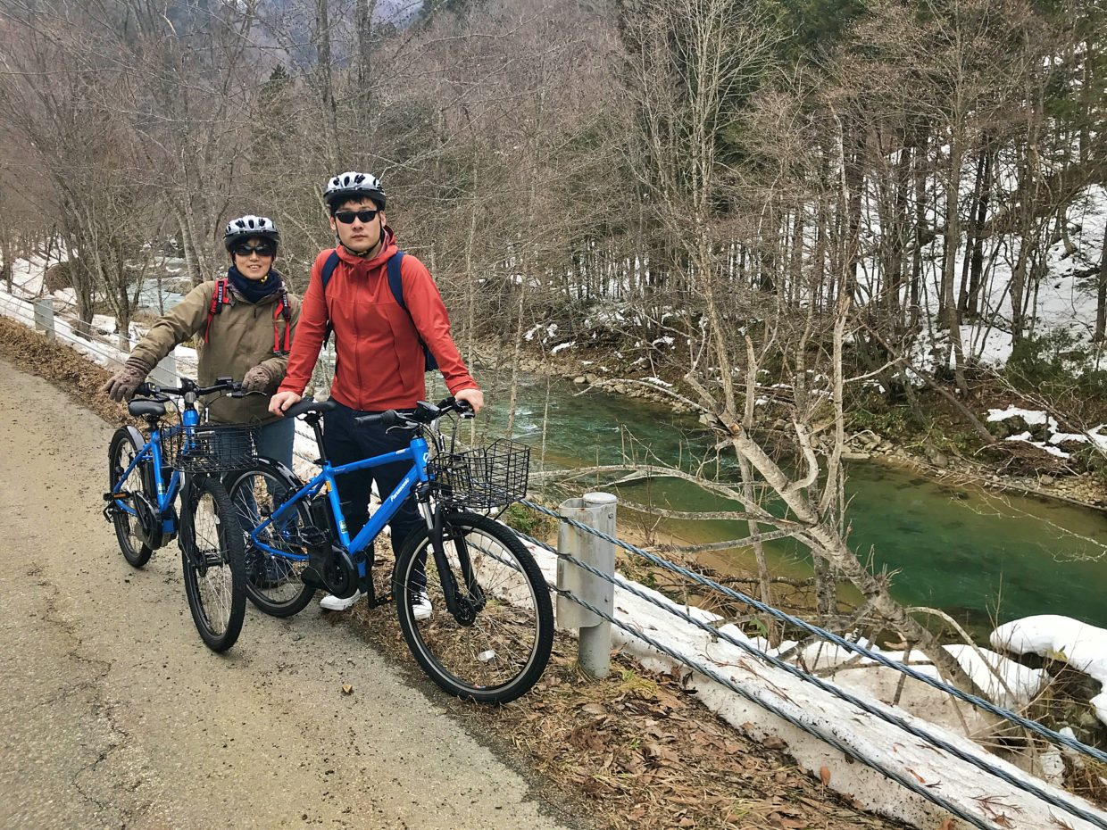 Bike tourists by the crystal river in Takayama