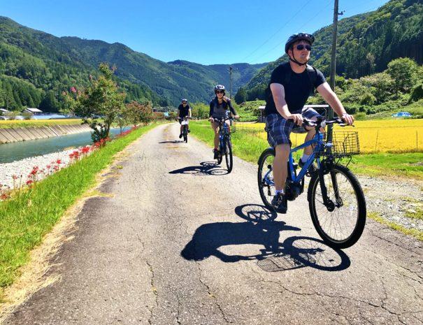 飛騨の川沿いでサイクリングを楽しむインバウンド旅行者