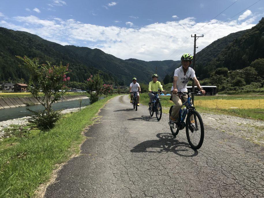 馬瀬川沿いを電動自転車で走る日本人観光客