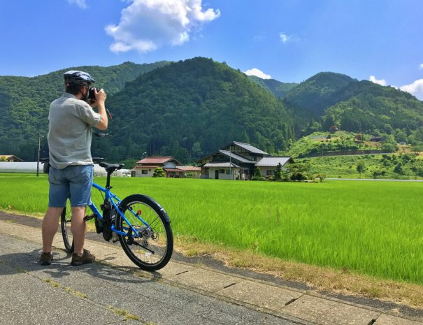 田園風景を撮影するサイクリングツアー参加者