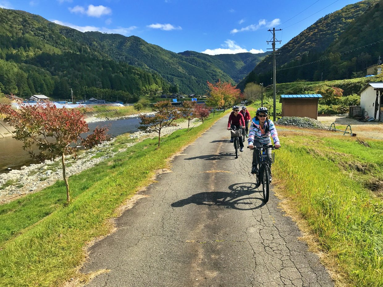 Australian tourists cycling along the river in Japan