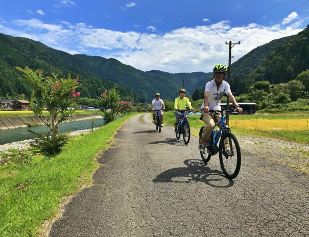 Japanese tourists enjoy cycling in the countryside of Japan