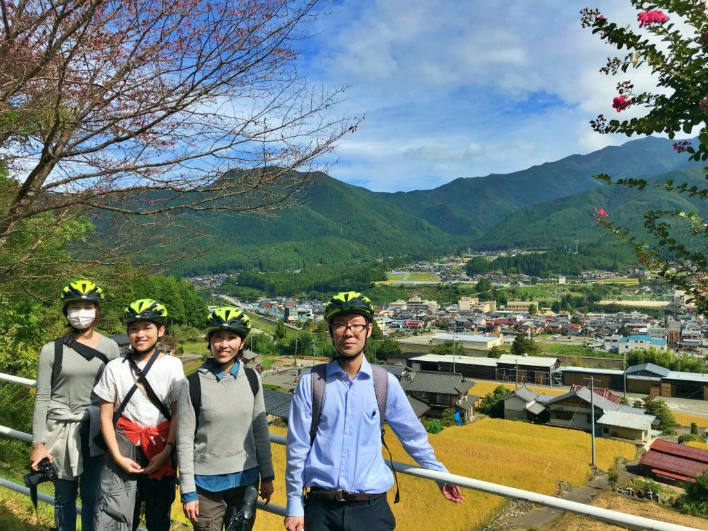 黄金色の田んぼと飛騨の山々をバックに写真撮影する国内観光客