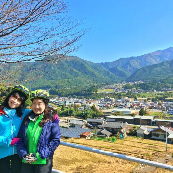 田んぼと飛騨の山々をバックに写真撮影する国内観光客